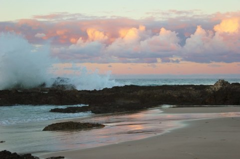 Waves crash on Snapper Rocks at sunset in Coolangatta, Gold Coast, Australia