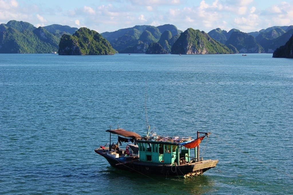 A fishing boat sails past us on our Halong Bay Cruise in Vietnam