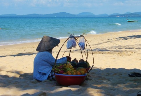 Fruit vendor resting on sand at Long Beach, Phu Quoc, Vietnam