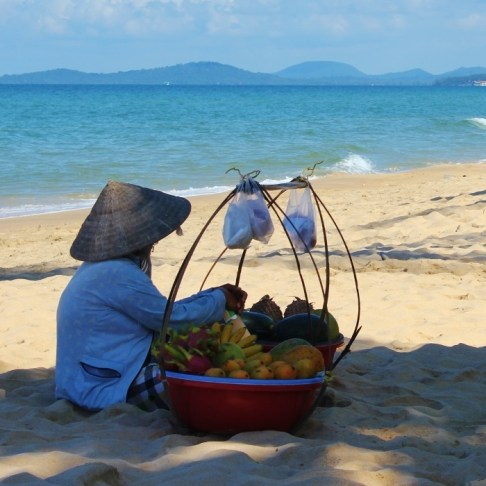 Fruit vendor resting on sand at Long Beach, Phu Quoc, Vietnam
