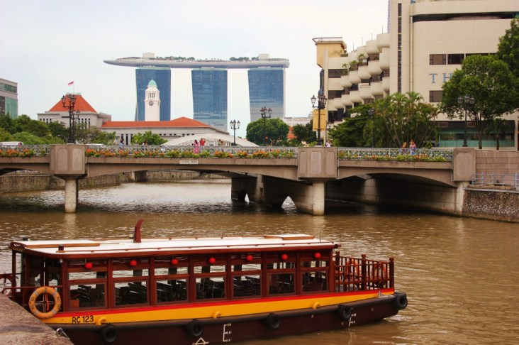 Traditional boat on Singapore River with view of Marina Bay Sands in Singapore