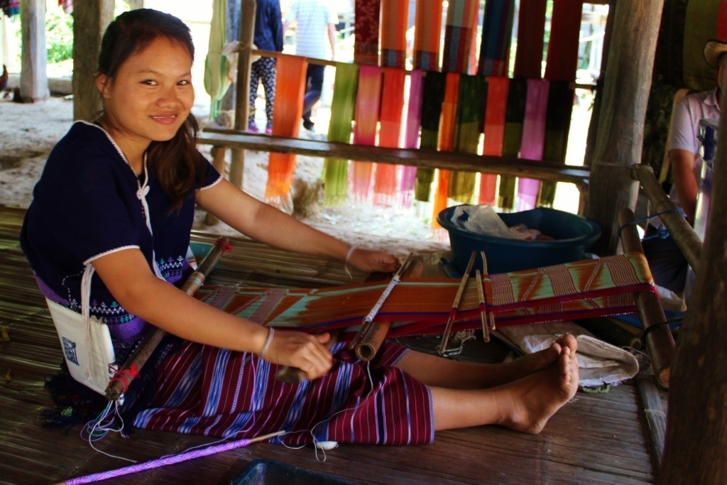 Hill tribe girl uses loom to weave clothing in Chiang Mai, Thailand