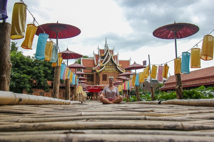 Woman sitting on bamboo bridge at Chedlin Temple in Chiang Mai, Thailand