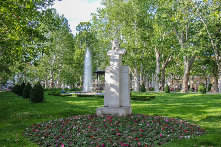 Statue surrounded by flowers in Green Horseshoe Park in Zagreb, Croatia