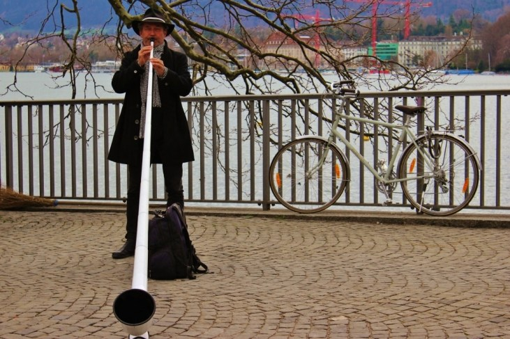 Man plays the alphorn on Lake Zurich, Zurich, Switzerland JetSettingFools.com