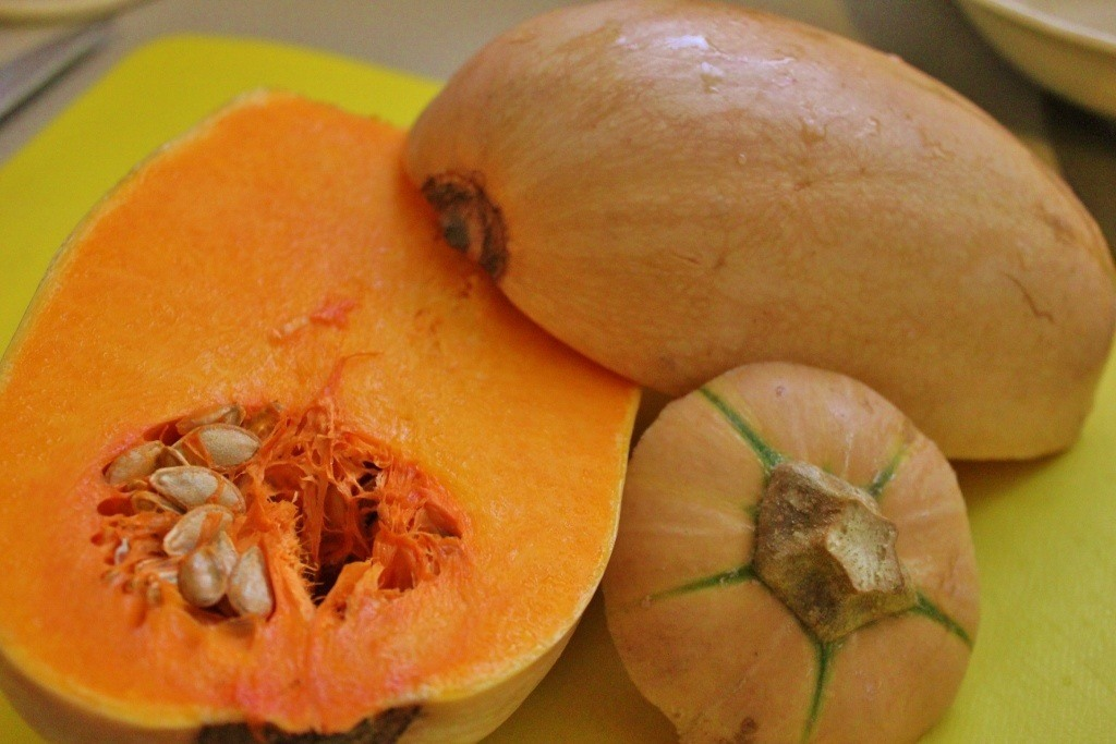 The first step to making pumpkin soup is to peel and cube pumpkin, saving the seeds.