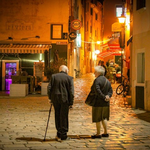 Elderly couple walks on cobblestone lanes in Old Town Rovinj, Croatia