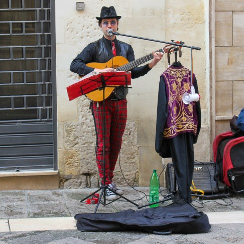 Man plays guitar on street in Lecce, Italy