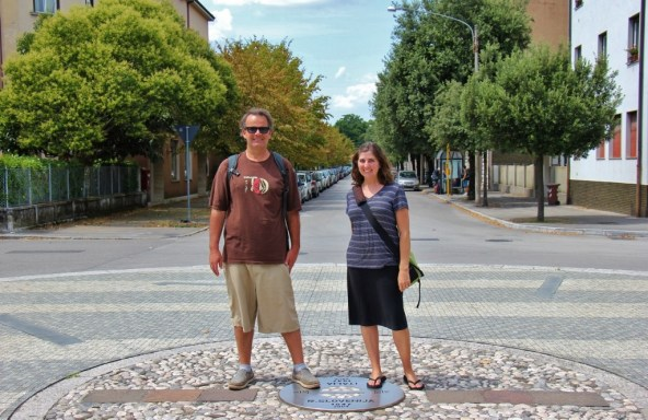 JetSetting Fools in Europe Square standing on the border marker between Italy and Slovenia