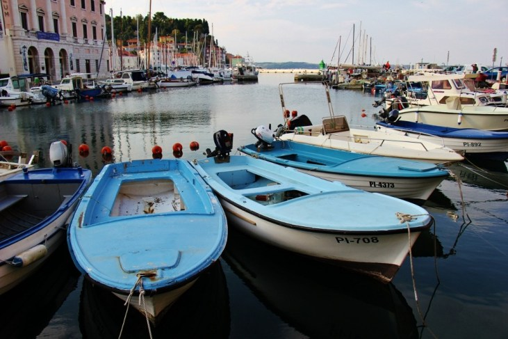 Fishing boats bob on water in harbor in Piran, Slovenia