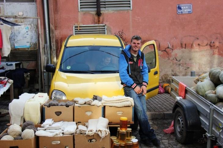 Young man smoking cigarette sells honey and wool from car, Green Market, Prishtina, Kosovo