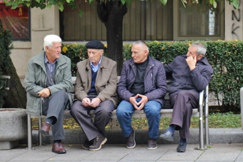 Old men sitting and talking on Mother Teresa Boulevard in Prishtina, Kosovo