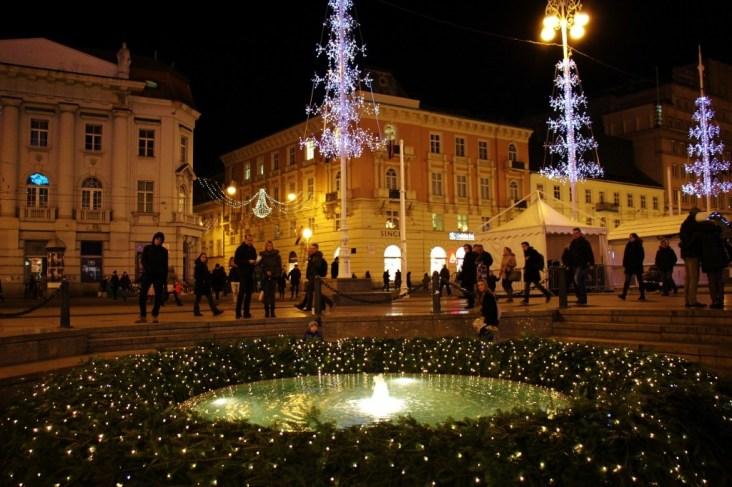 Advent wreath circles Mandusevac Fountain on Ban Jelacic Square during Christmas in Zagreb, Croatia