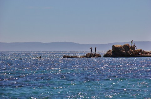 People standing on rocks in the sea at Bacvice Beach in Split, Croatia