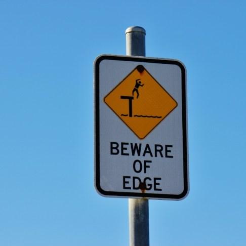 Yellow Beware of Edge sign on Great Ocean Road, Australia, JetSettingFools.com