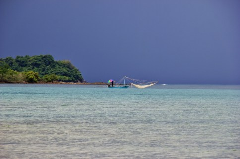 Fisherman with colorful umbrella at Kai Bae Beach on Koh Chang, Thailand