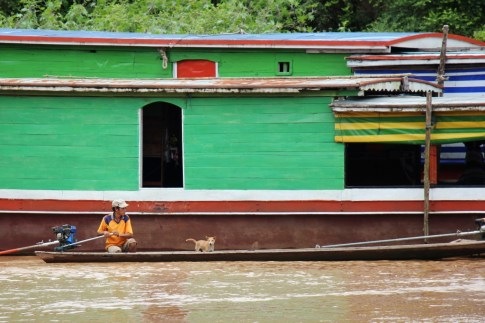 Fisherman with dog on boat on Mekong River, Laos