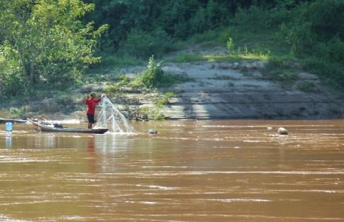 Fisherman tends to nets on Mekong River, Laos