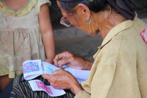 Woman stitches patternn in Ban Kok Eak village, Laos