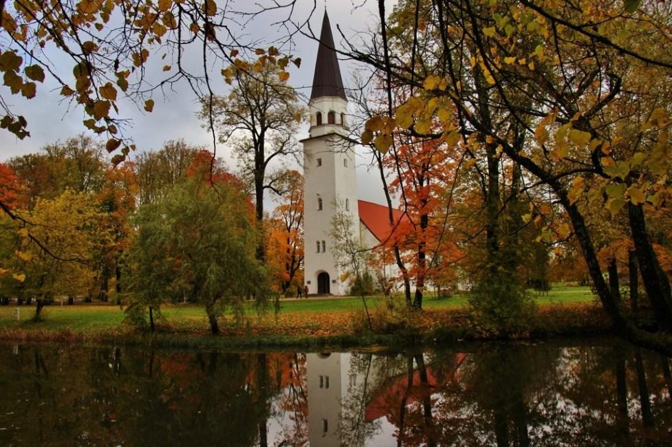 White bell tower of Sigulda Lutheran Church reflecting on pond in Sigulda, Latvia