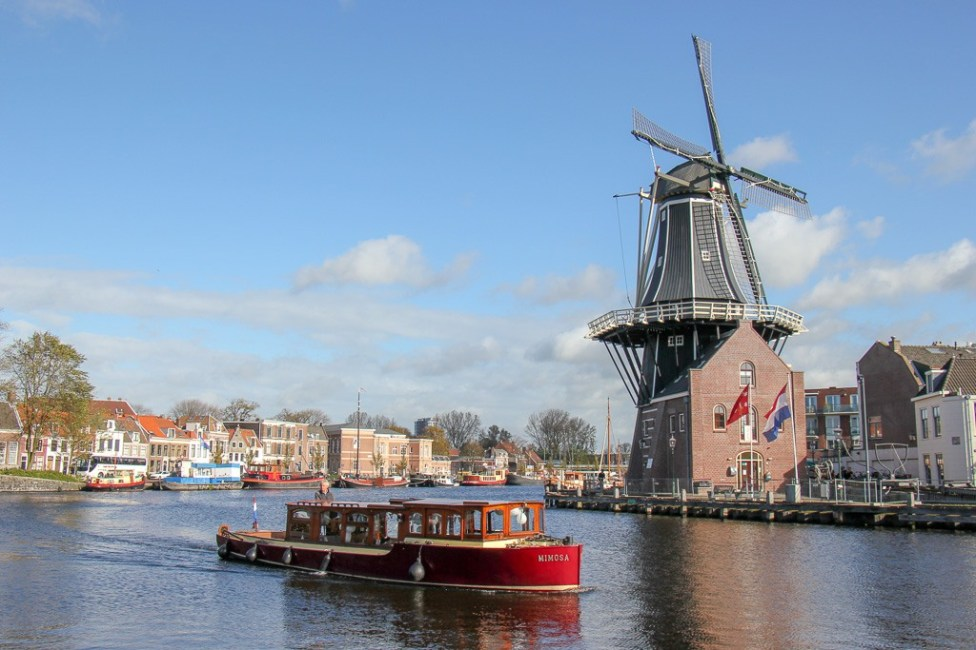 Red tourist boat and Haarlem Windmill in Haarlem, Netherlands