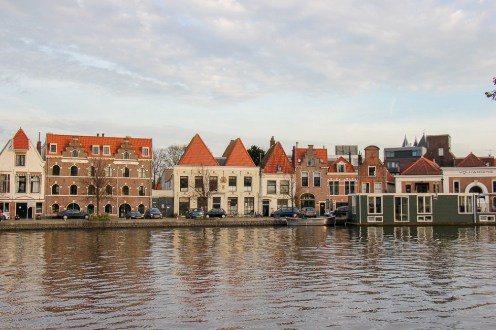 Houseboat and riverfront buildings on Spaarne River in Haarlem, Netherlands