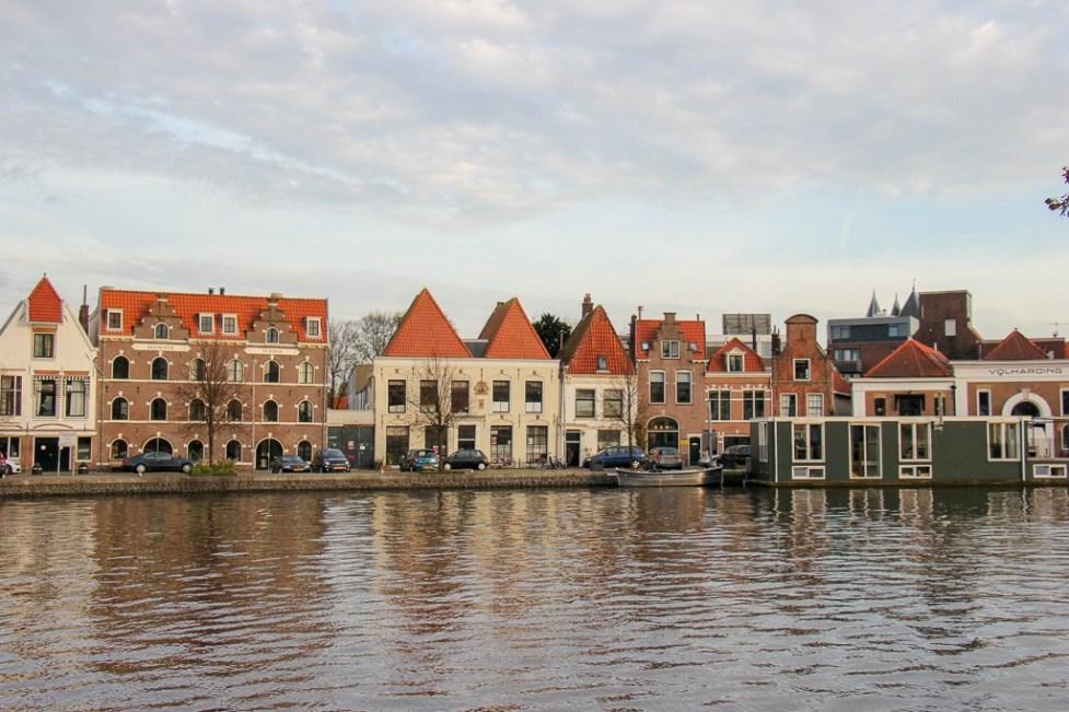 Houseboat and riverfront buildings on Spaarne River in Haarlem, Netherlands
