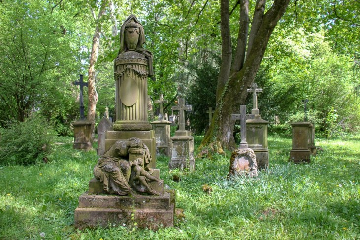 Gravestones in overgrown grounds at Alter Friedhof Old Cemetery in Freiburg, Germany