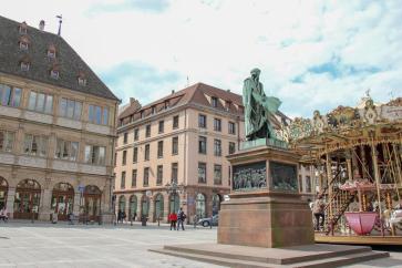 Statue of Gutenberg and carousel on Gutenberg Square in Strasbourg, France