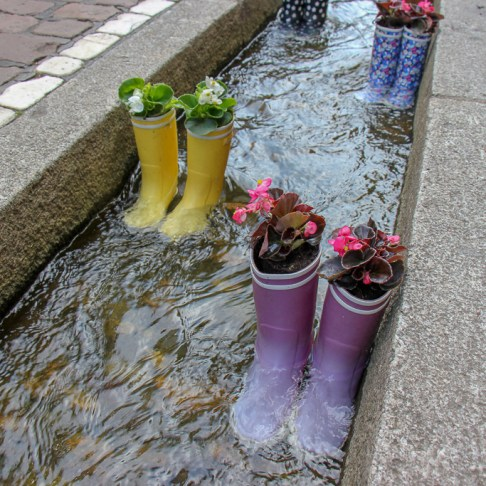 Rainboot flowerpots in Bachle in Freiburg, Germany