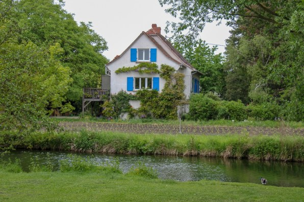 White house with blue shutters on River in Colmar, France