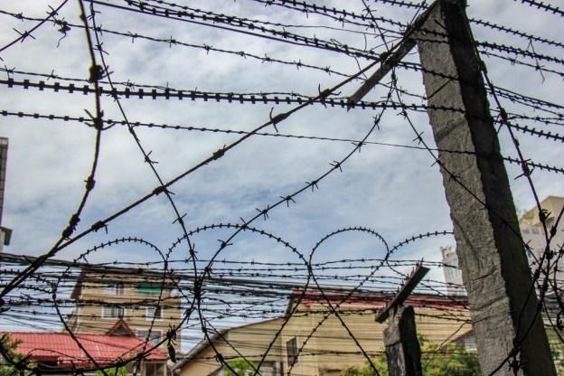 Barbed wire surrounds S21 Museum in Phnom Penh, Cambodia
