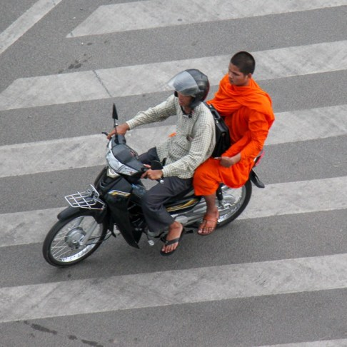 Monk gets a ride on a cycle in Phnom Penh, Cambodia