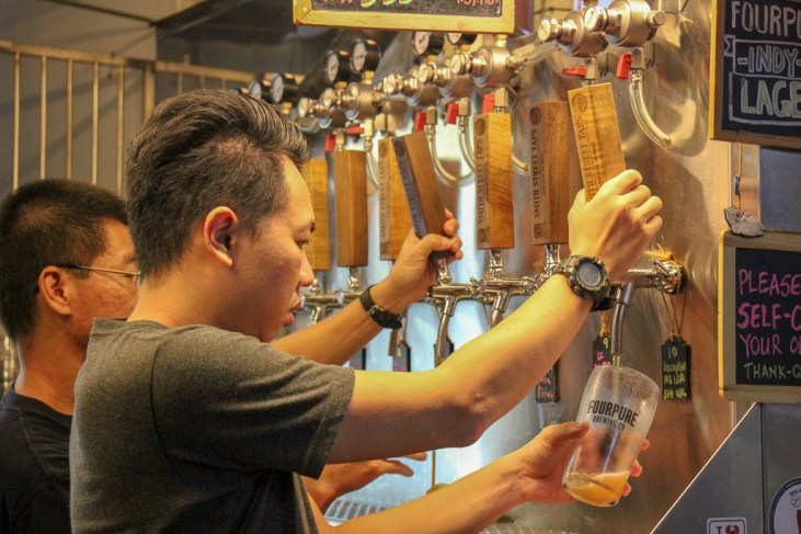 Bartender pours beer at Smith Street Taps craft beer hawker stall in Chinatown Food Complex in Singapore