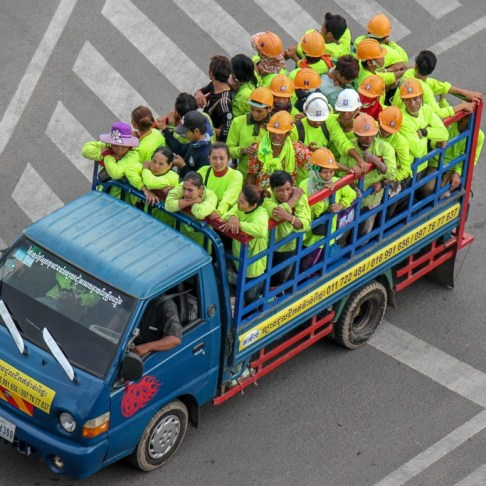Workers wearing florescent vests in truck bed in Phnom Penh, Cambodia