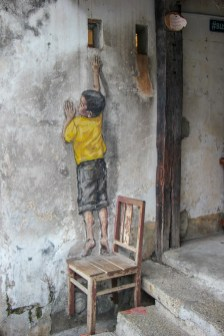 Boy on chair reaching up street art mural in Geroge Town, Penang, Malaysia