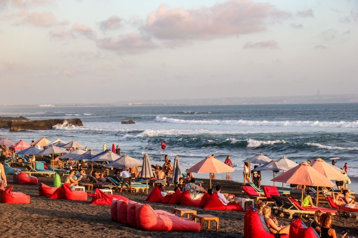 Tourists relax on bean bags and loungers on Echo Beach in Canggu, Bali, Indonesia