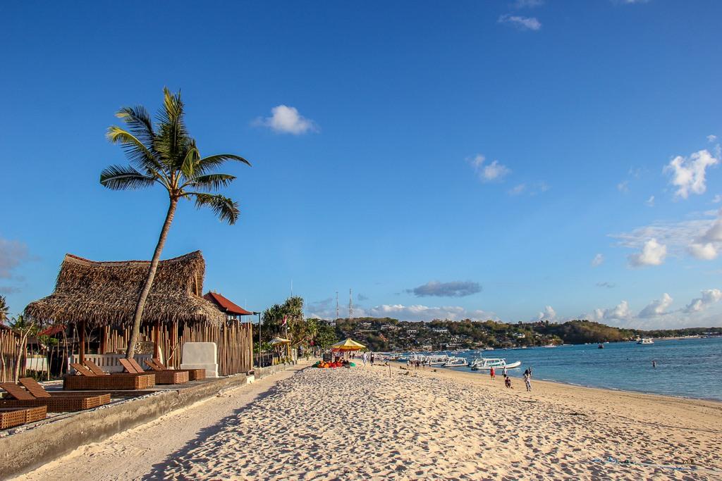 Palm tree and beach house on Jungut Batu Beach on Nusa Lembongan, Bali, Indonesia