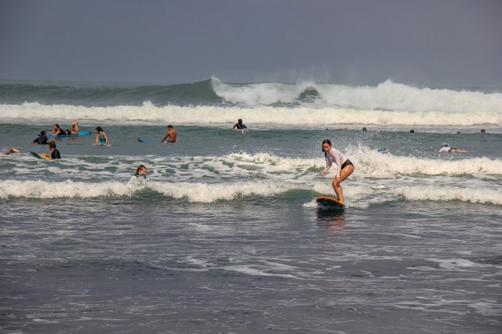Tourists learn to surf on Batu Bolong Beach in Canggu, Bali, Indonesia