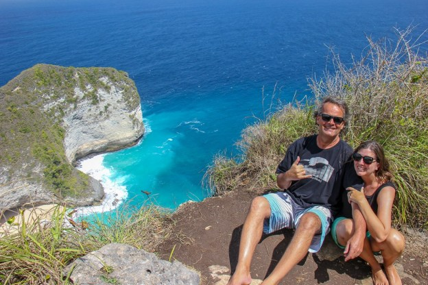 Sitting on the cliff overlooking Kelingking Beach on Nusa Penida, Bali, Indonesia