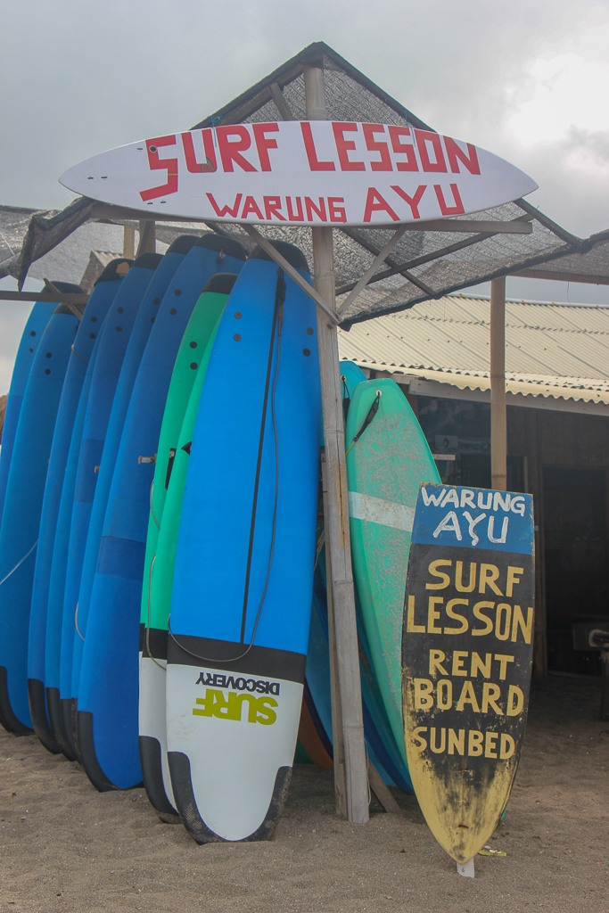 Surf boards for rent and surf lessons sign at Batu Bolong Beach in Canggu, Bali, Indonesia