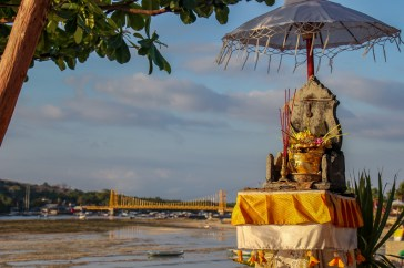 Small temple shrine and Yellow Bridge at Sea Breeze Bar on Nusa Ceningan, Bali, Indonesia