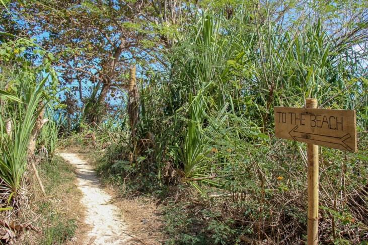 Wood beach sign on path in Uluwatu, Bali, Indonesia