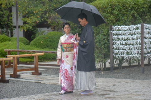 Couple in traditional dress under umbrella in Kyoto, Japan