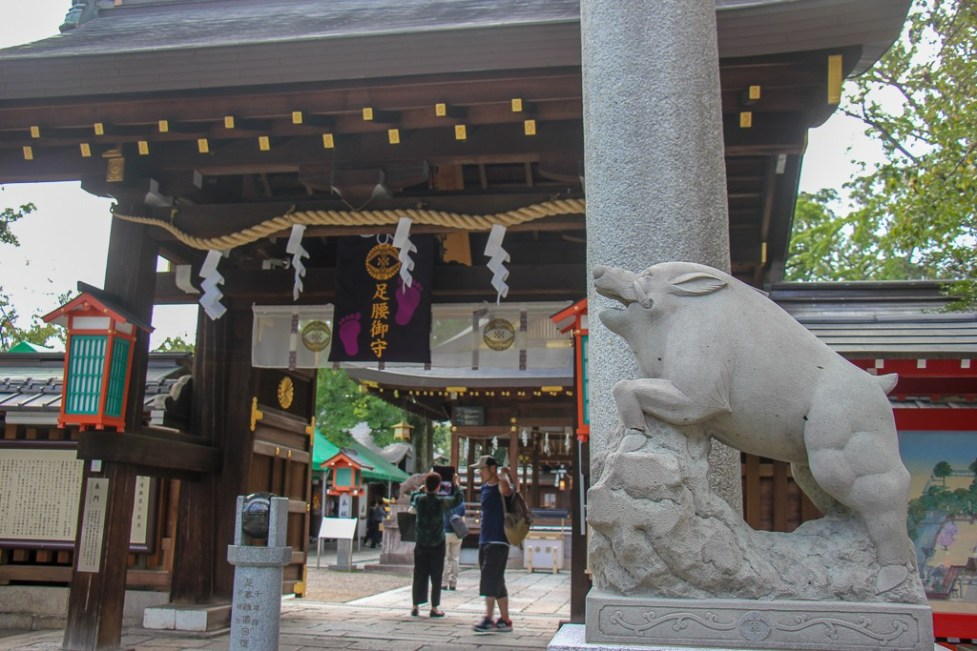Pig sculptures guard entrance to Go'o Shinto Shrine in Kyoto, Japan