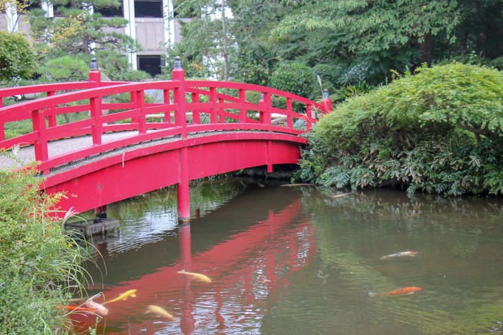 Red bridge over koi pond at Hotel New Otani's Garden in Tokyo, Japan
