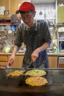 Man cooks Japanese savory pancake at Okonomiyaki Katsu in Kyoto, Japan