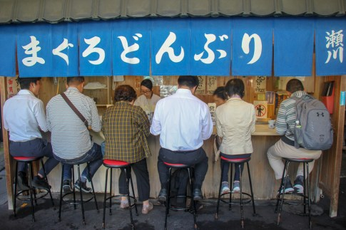 Tsukiji Outer Market food stall restaurant with seated patrons in Tokyo, Japan