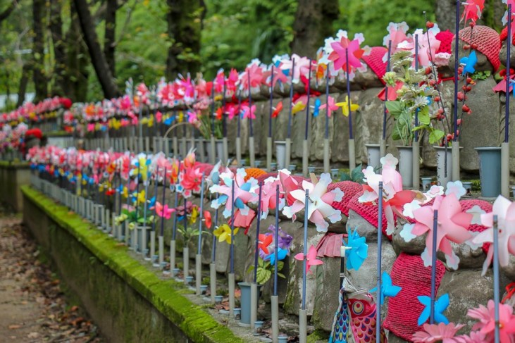 Statues with pinwheels at Zojoji Temple in Tokyo, Japan
