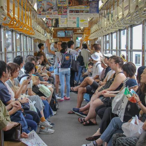 People sitting on tram in Kyoto, Japan